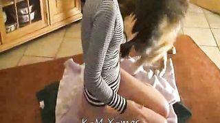 Petite dark brown in dark and white sweater takes her brown dog on kitchen floor