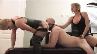 Two taskmaster honeys in black leather using a dong on a ready centre mature chap