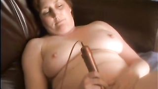 Mature redhead lying back watching porn and cumming